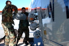 """Maintainers from the New York Air National Guard's 109th Airlift Wing attach jet-assisted takeoff , or JATO, bottles to an LC-130 Hercules """"skibird"""" July 24 on the flight line at Kangerlussuaq Airport, Greenland. JATO provides a few extra knots of speed to pull the aircraft's nose up from skiways on the Greenland ice sheet. (U.S. Air Force photo/Tech. Sgt. Mike R. Smith)"""