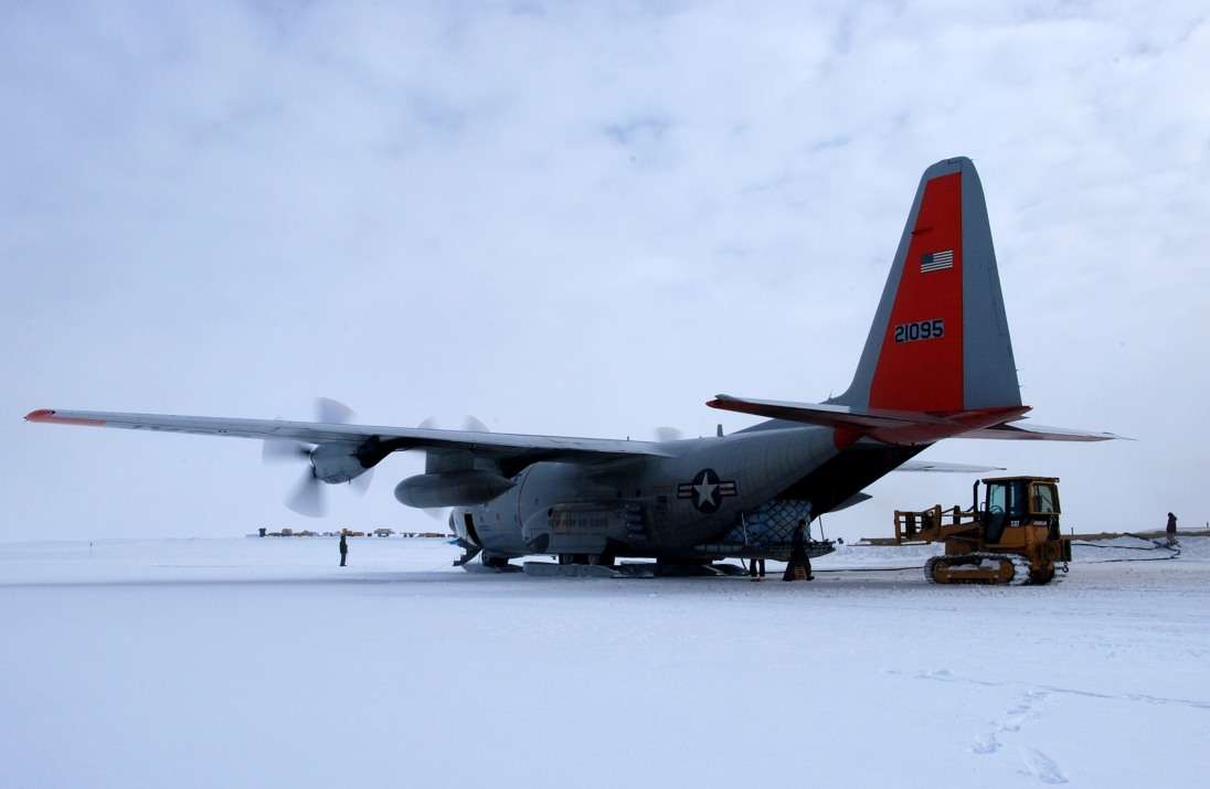 """An LC-130 Hercules from the New York Air National Guard's 109th Airlift Wing is loaded with cargo at Camp Summit July 24 on the Greenland Ice Sheet. The wing's gray and orange """"skibirds"""" are the world's largest ski-equipped cargo aircraft. (U.S. Air Force photo/Tech. Sgt. Mike R. Smith)"""