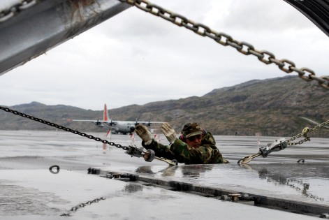 """Master Sgt. Ray Boyea from the New York Air National Guard's 109th Airlift Wing directs cargo onto an LC-130 Hercules July 26 on the flight line at Kangerlussuaq Airport, Greenland. The wing's gray and orange """"skibirds"""" are the world's largest ski-equipped cargo aircraft. (U.S. Air Force photo/Tech. Sgt. Mike R. Smith)"""