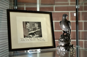 """MCGHEE TYSON AIR NATIONAL GUARD BASE, Tenn. – Memorabilia of U.S. Air Force Maj. Gen. I.G. Brown is displayed in the lobby of Patriot Hall here at the I.G. Brown Training and Education Center. In the framed photo, Brown as a brigadier general holds a model aircraft with then Lt. Gen. Joe W. Kelly, later the first four star commander of the U.S. Air Force's Military Air Transport Service. Kelly's autograph reads, """"My best regards to Gen. I.G. Brown."""" Brown later became first Director of the Air National Guard and is credited with founding the Center dedicated in his name. (U.S. Air National Guard photo by Master Sgt. Kurt Skoglund/Released)"""