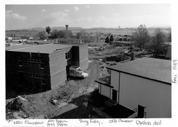 Construction of the classroom building (left) at the Professional Military Education Center on McGhee Tyson Air National Guard Base in East Tennessee, made for close quarters and muddy areas during the Fall of 1989. Phase One, which also included the new NCO academy dormitory were ahead of schedule; meanwhile, bulldozers and dump trucks had started moving dirt for Phase Two in the construction, which included the multi-media building (Spruance Hall) and multi-purpose building (Wilson Hall). (U.S. Air National Guard file photo)